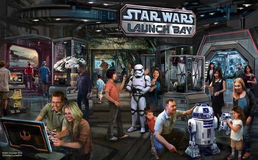 Families exploring Star Wars Launch Bay: robots, exhibits, computer screens.